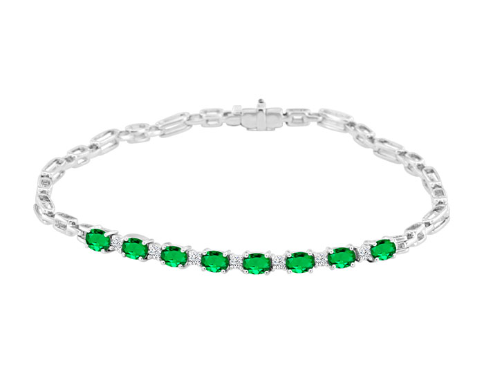 Oval shape emerald and round brilliant cut diamond bracelet in 18k white gold.