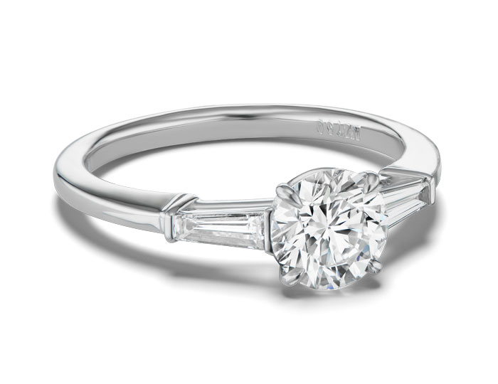 Round brilliant cut and tappered baguette diamond engagement ring in platinum.