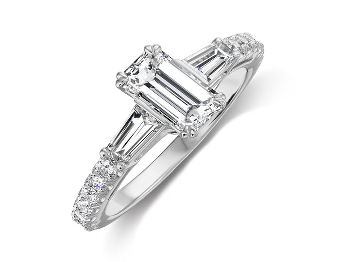 Bez Ambar emerald cut, tappered baguette, and round brilliant cut diamond engagement ring in platinum.