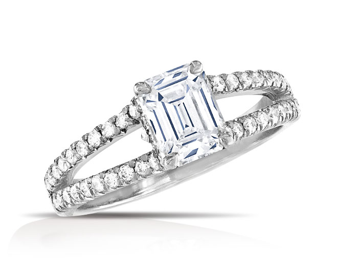 Emerald cut and round brilliant cut diamond engagement ring in platinum.