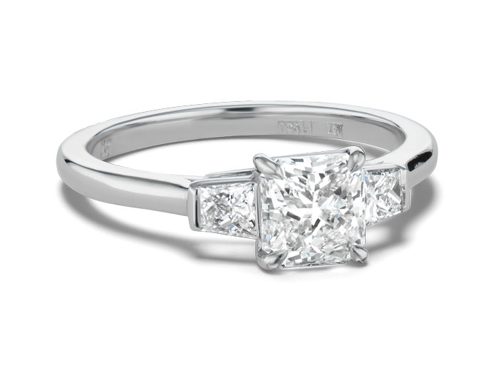 Radiant cut and trapezoid diamond three-stone engagement ring in platinum.