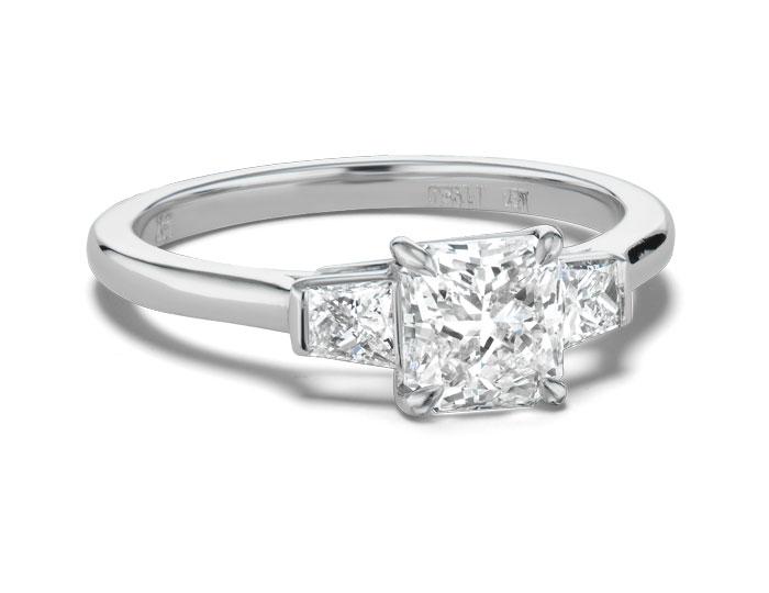 Bez Ambar radiant cut and trapezoid cut diamond three-stone engagement ring in platinum.