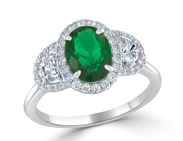 Oval cut emerald and half moon cut and round brilliant cut diamond ring in 18k white gold.