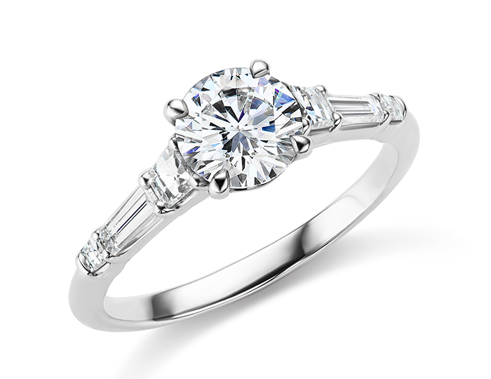 Round brilliant cut, tappered baguette cut and blaze cut diamond engagement ring in platinum.