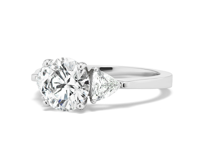 Round brilliant cut and trillion cut diamond engagement ring in platinum.