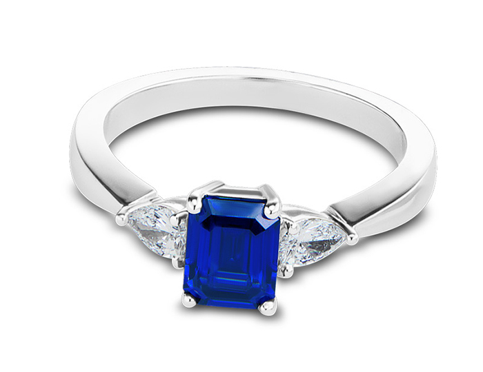 Emerald cut sapphire and pear shape diamond ring in 18k white gold.