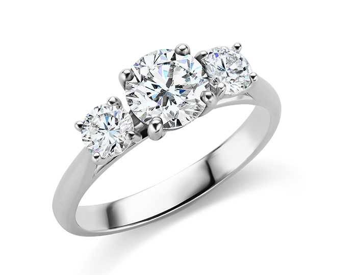 Round brilliant cut diamond three-stone engagement ring in platinum.