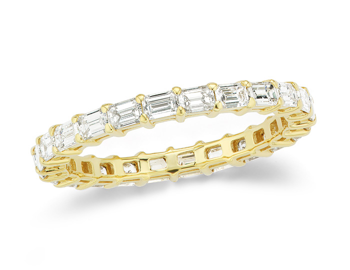 Emerald cut diamond eternity band in 18k yellow gold.