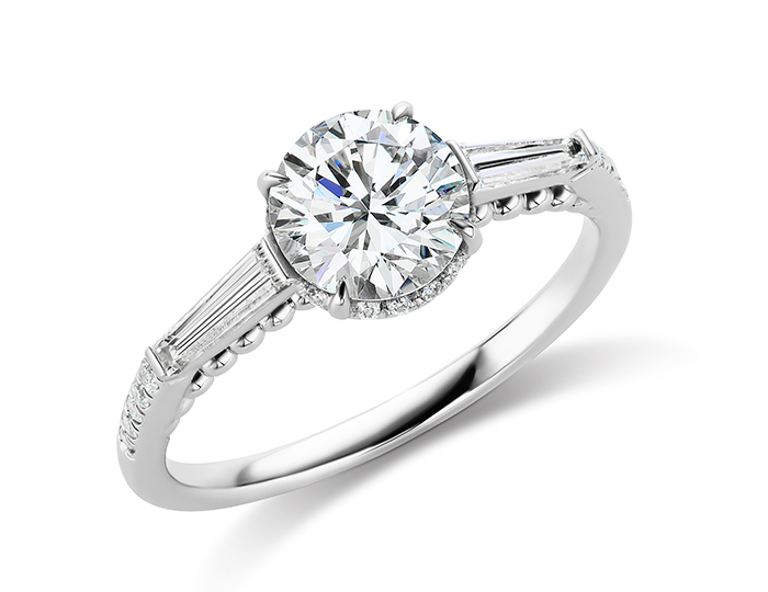Round brilliant cut and baguette cut diamond engagement ring in 18k white gold.