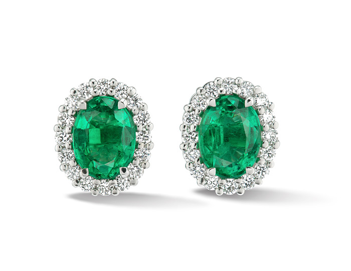 Oval emerald and round brilliant cut diamond earrings in 18k white gold.