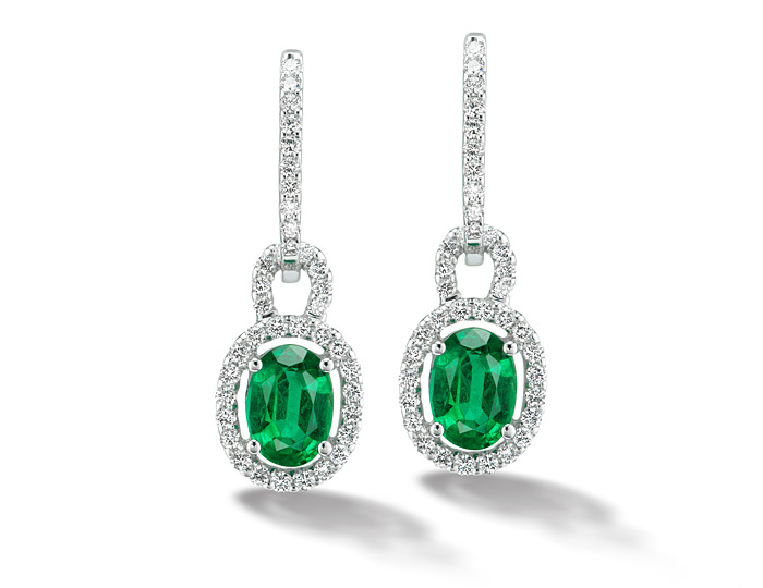 Oval shape emerald and round brilliant cut diamond earrings in 18k white gold.
