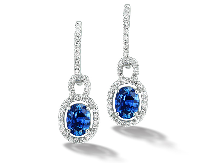 Oval shape sapphire and round brilliant cut diamond earrings in 18k white gold.