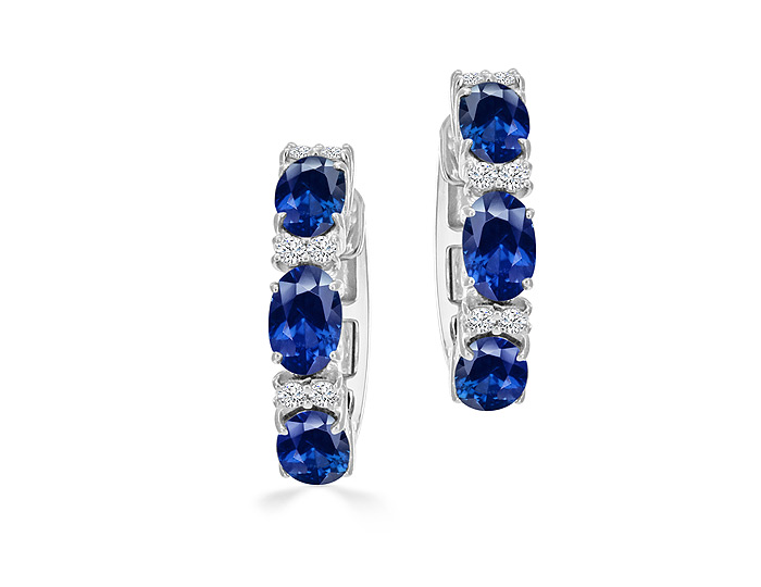 Oval shape sapphire and round brilliant cut diamond hoop earrings in 18k white gold.