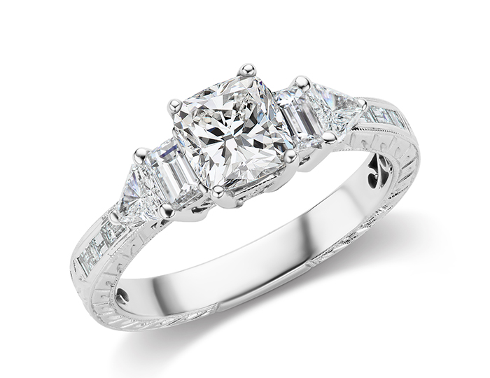 Cushion center diamond engagement ring with trillion, baguette and emerald cut diamonds set in 18k white gold.