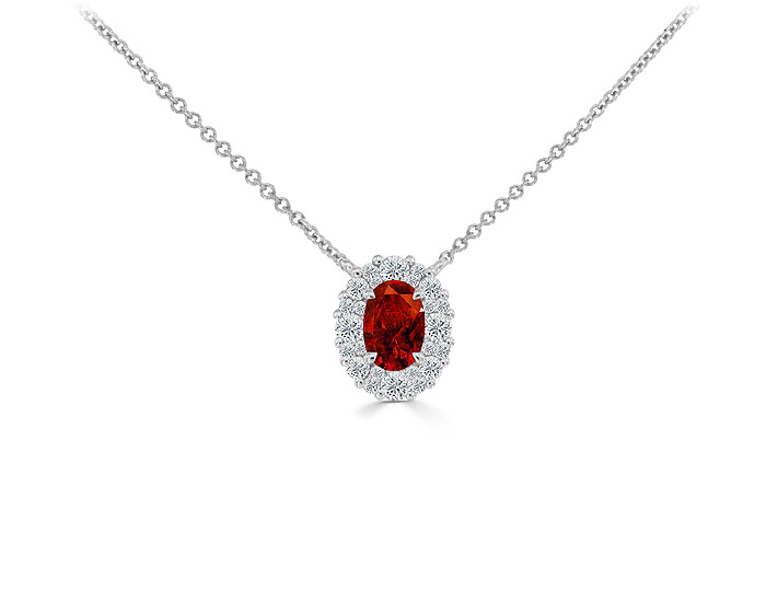 Oval shape ruby and round brilliant cut diamond pendant in 18k white gold.