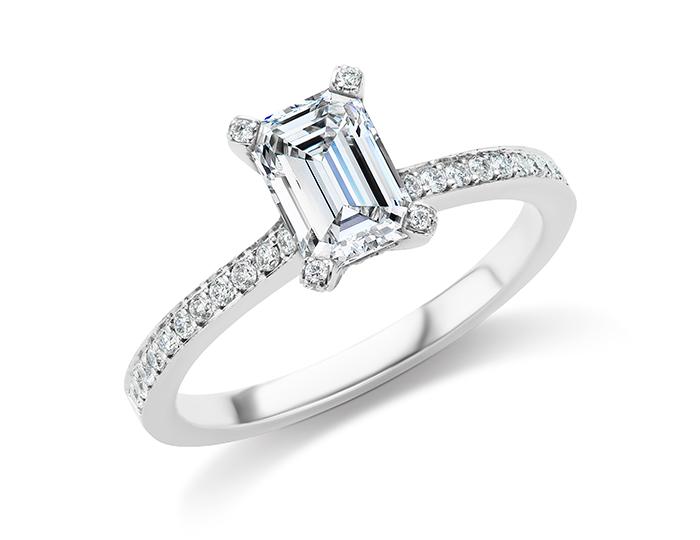 Emerald cut center diamond and round brilliant cut diamond engagement ring in platinum.