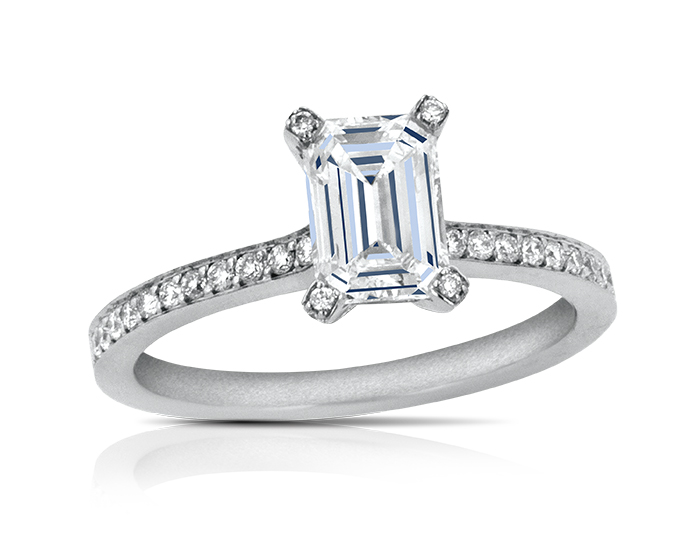 Emerald cut center diamond and round brilliant cut diamond engagement ring in platinum.