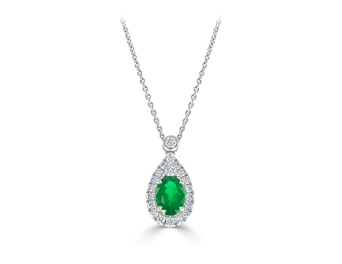 Oval emerald and round brilliant cut diamond pendant in 18k white gold.