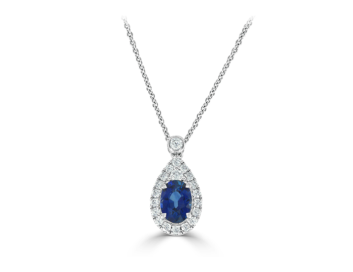Oval shape sapphire and round brilliant cut diamond pendant in 18k white gold.