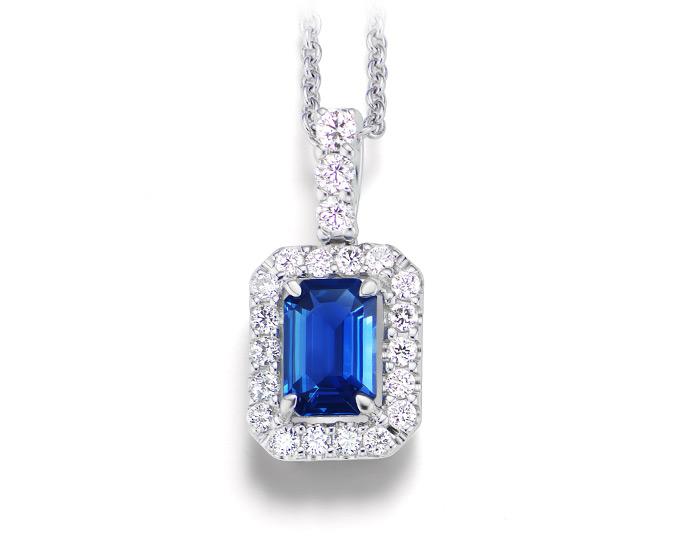 Emerald cut sapphire and round brilliant cut diamond pendant in 18k white gold.