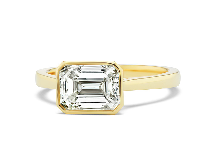 Emerald cut diamond engagement ring in 18k yellow gold.