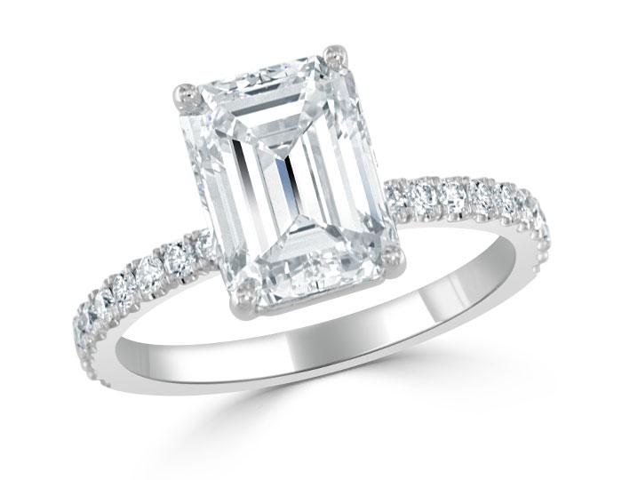 Emerald cut and round brilliant cut diamond engagement ring in platinum.