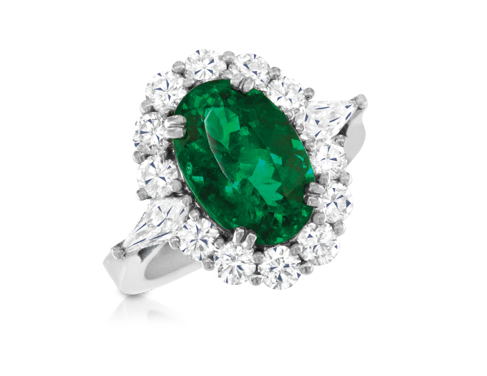 Emerald with kite and round brilliant cut diamond ring in 18k white gold.