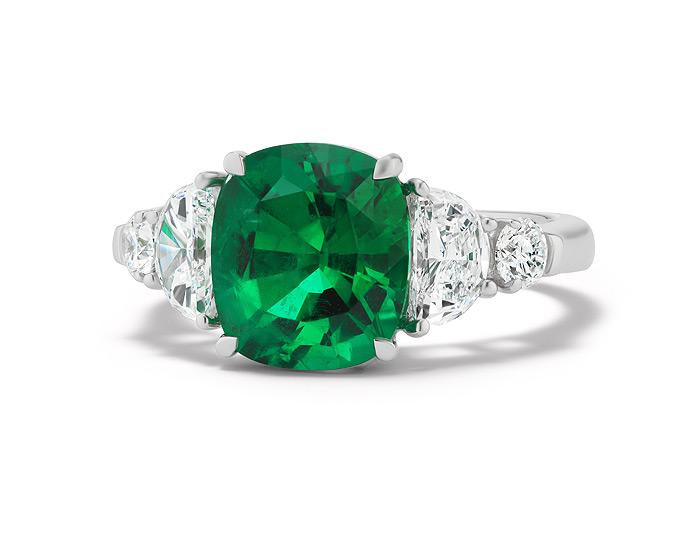 Cushion cut emerald, half-moon cut diamond and round brilliant cut diamond ring in 18k white gold.