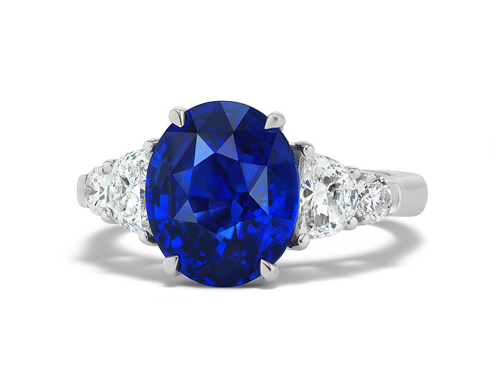 Oval sapphire, half-moon cut diamond and round brilliant cut diamond ring in 18k white gold.
