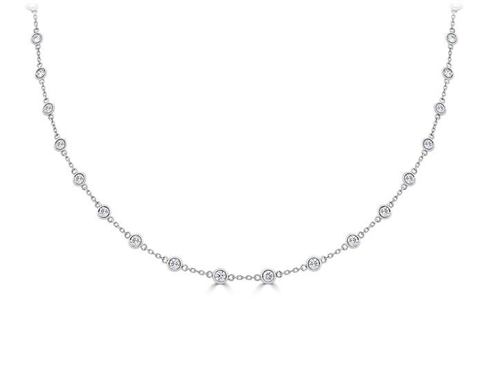 Round brilliant cut diamond bezel necklace in 18k white gold.