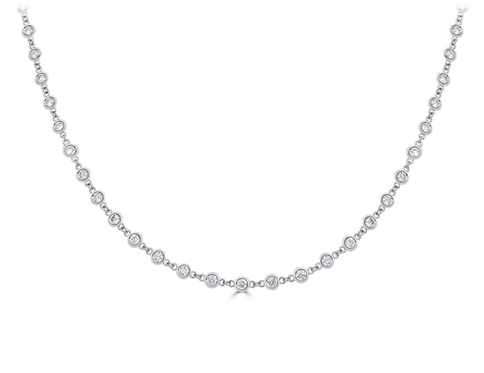 "Round brilliant cut diamond bezel necklace in 18k white gold, measuring 16"" in length, diamonds spaced 1/4"" apart."