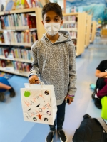 kid holding halloween craft bag