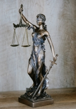 a metal statue of Justice, a blindfolded woman holding scales and a sword