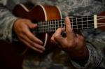 Individual playing a ukulele