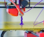 3D printer printing a purple spiral tower