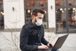 young white man wearing mask sitting on a city bench with his laptop