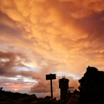 Mt. Washington Observatory tower surrounded by clouds reflecting golden-orange sunset
