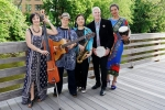 Five Women in colorful clothing, standing outdoors, each holding their instrument
