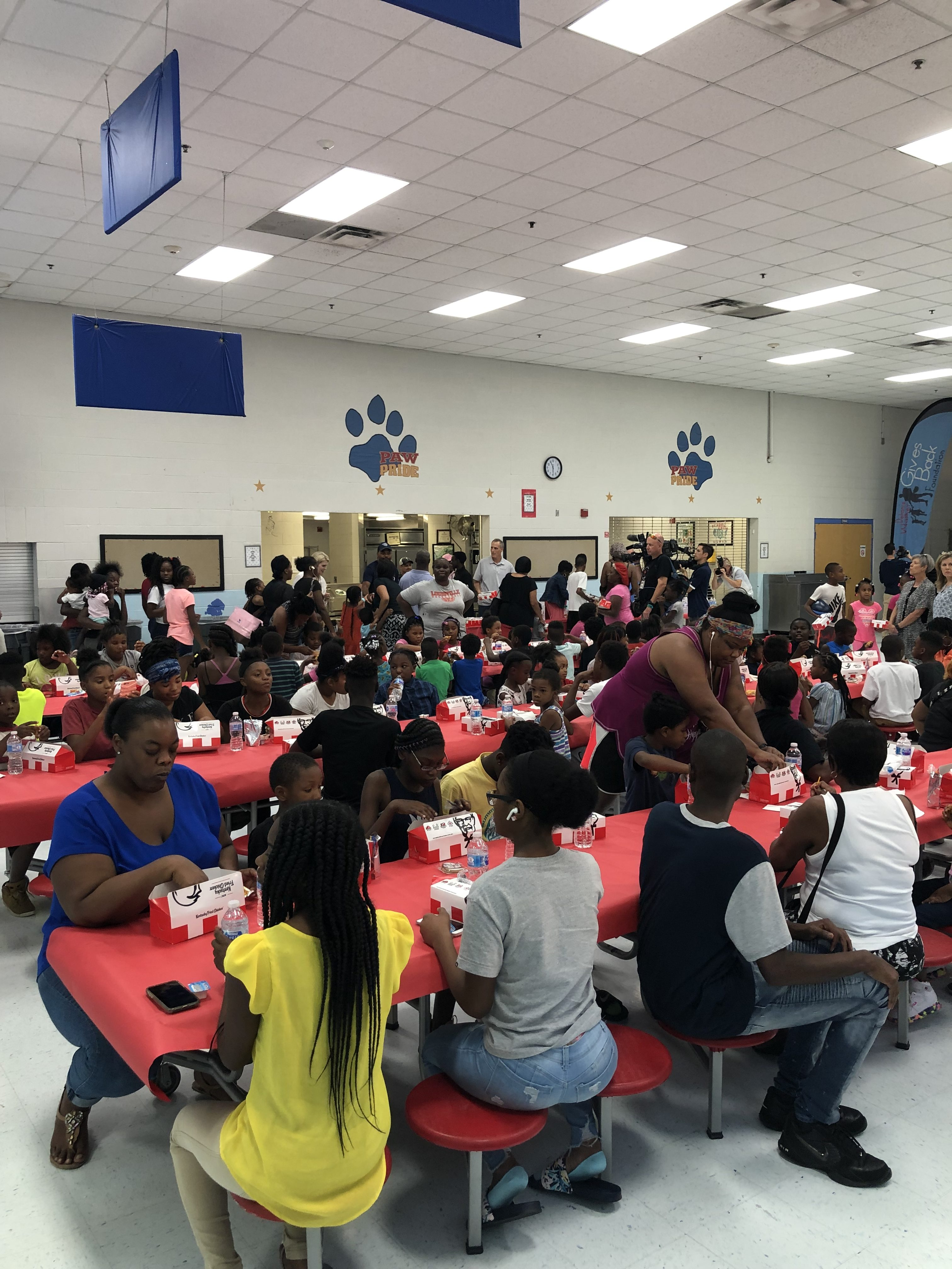 A cafeteria filled with young students and families eating KFC food