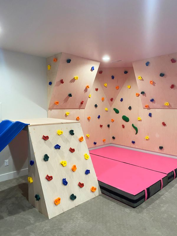 pink crash mat under climbing wall