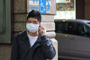 Man-covering-his-face-with-surgical-mask