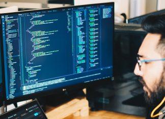 Um homem de barba e óculos usando dois computadores