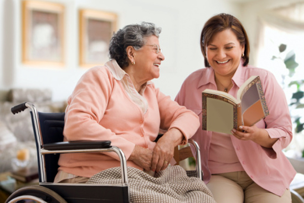 caregiver reading to woman in wheelchair