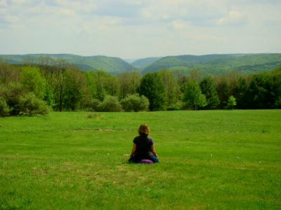 woman meditating in field at light on a hill retreat center