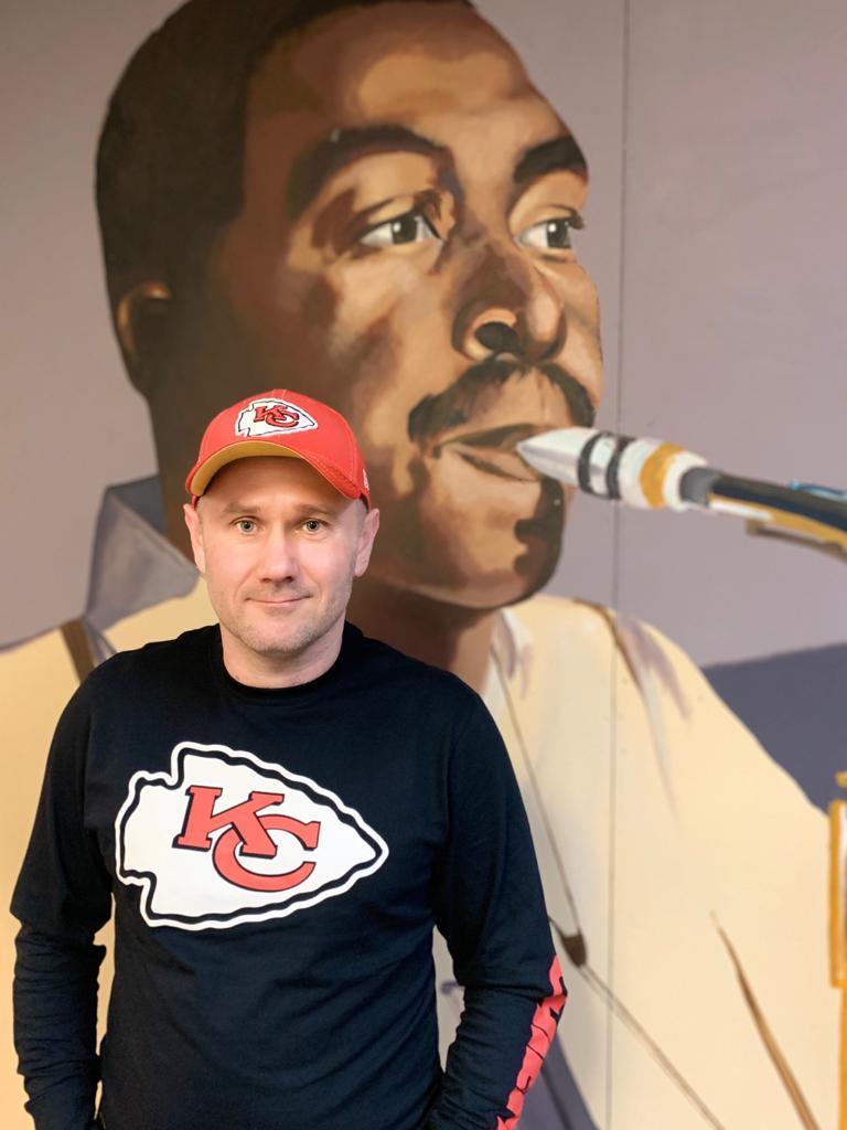 Sylwester Ostrowski in Front of a Charlie Parker Art at KKFI Studios in Kansas City-Half