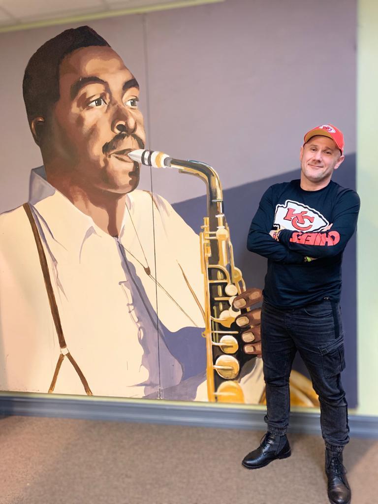 Sylwester Ostrowski in Front of a Charlie Parker Art at KKFI Studios in Kansas City-Full