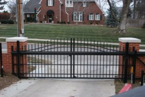 An overscallop cantilever gate set in a residential driveway with brick columns on either side