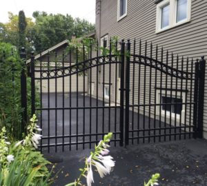 An aluminum swing gate situated near the side of a house, securing the back half of the house