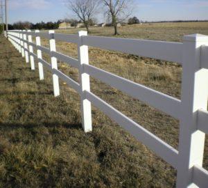 A white 3 rail ranch rail running along the edge of a vast field