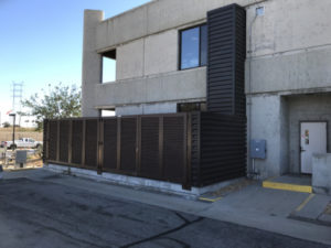 A metal louvered fence from PalmSHIELD forming an protected enclosure outside of a City of Los Angeles Department of Water and Power building